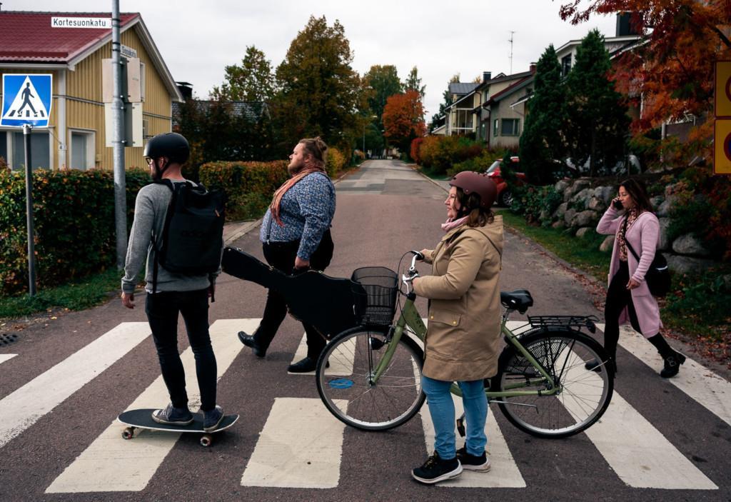Neljä ihmistä kävelee suojatien yli. Yksi heistä skeittaa, yksi taluttaa pyörää.